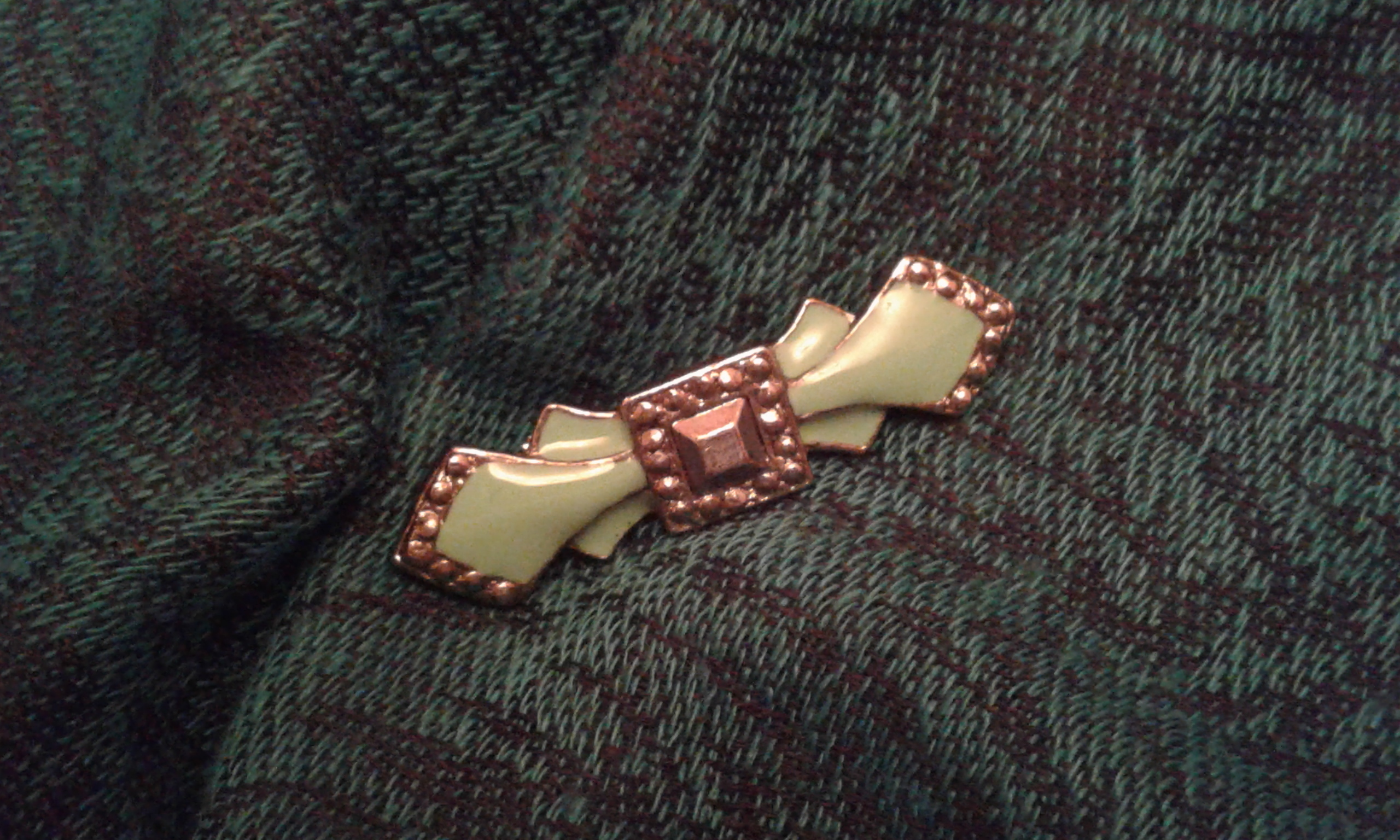 A green antique brooch on a cashmere shawl