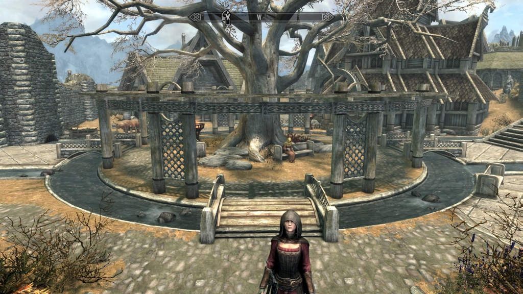 Skyrim Whiterun town centre with a local woman by a large tree surrounded by a circular stream and bridges.