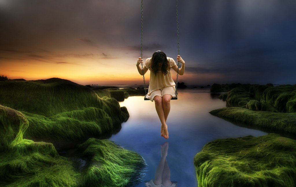 Image of a girl on a swing over water
